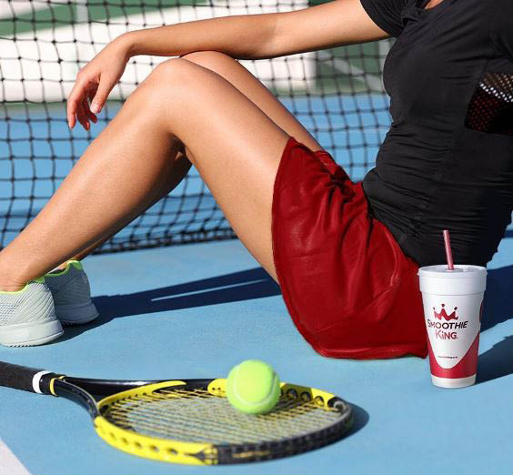 Woman relaxing after playing tennis with a Smoothie King drink