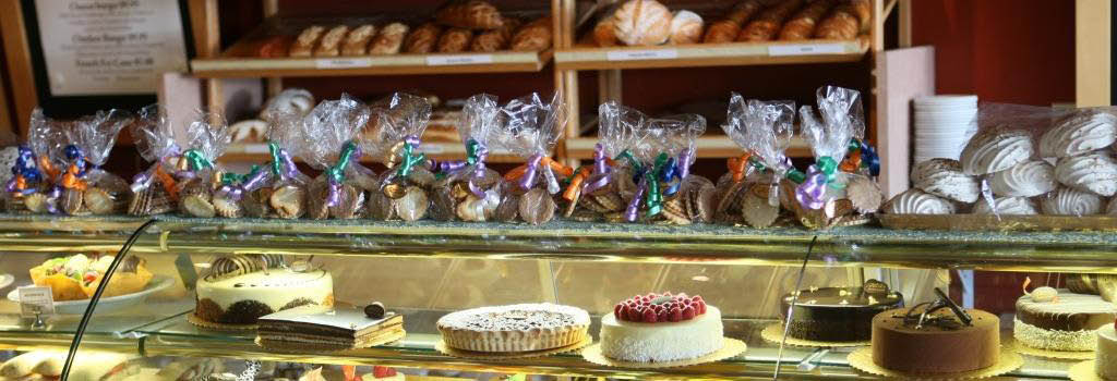 SoHo Cafe and Bakery display case with cakes, pastries, fresh bread and cookies banner