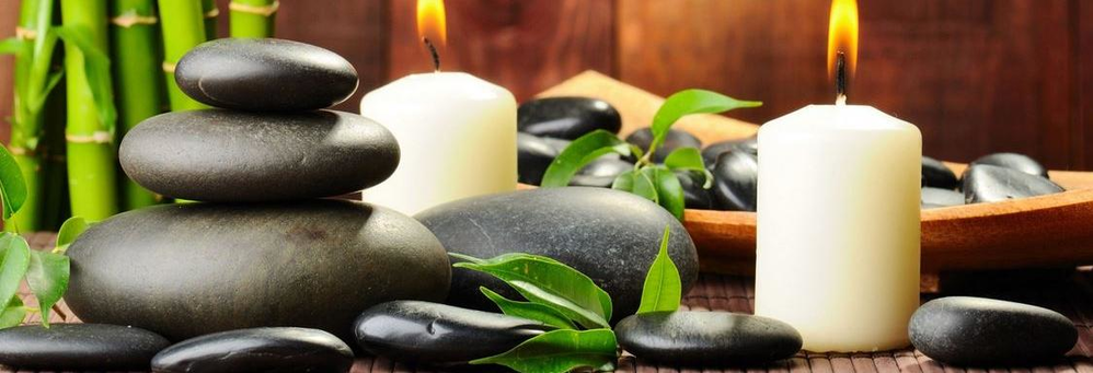 Hot stones for massage and lit candles banner