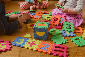 children playing on the floor with a colorful teaching foam puzzle; Southwest Child Care in Albuquerque