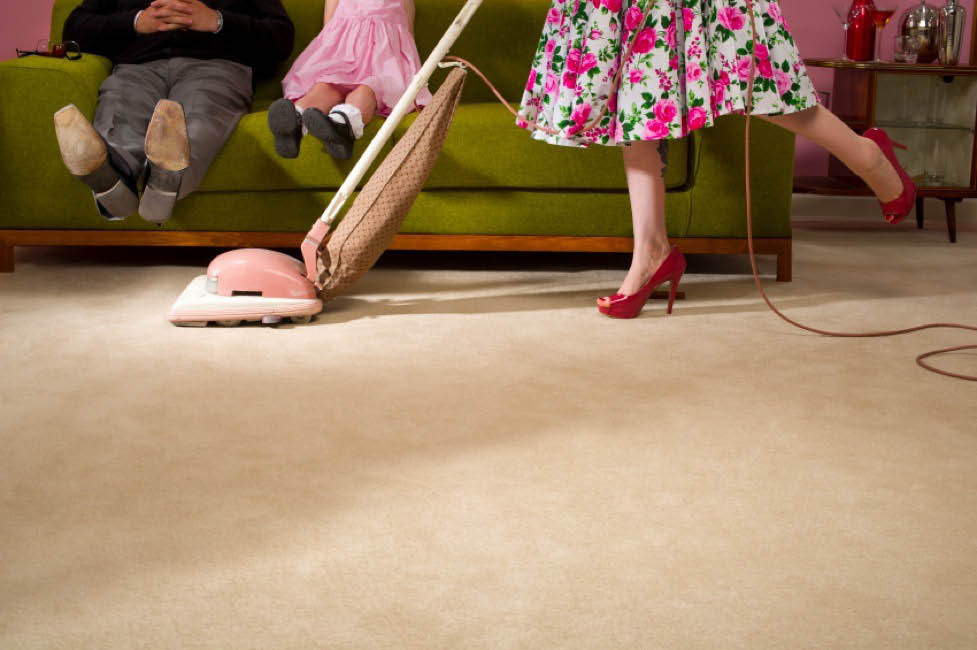 Vacuuming living room carpet