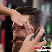 Stylist trimming a man's beard