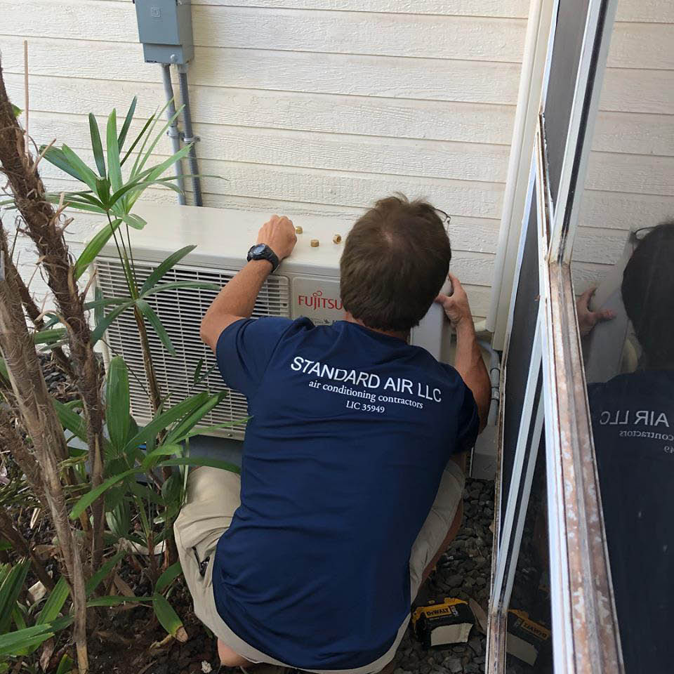 AC technician working on air conditioning unit
