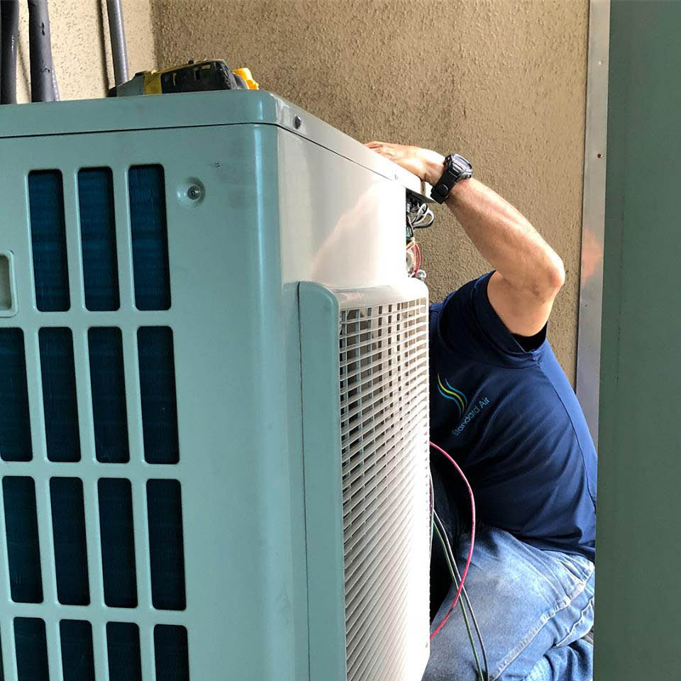 Air conditioner technician working on HVAC system