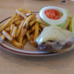 Double cheeseburger with fries served with melted cheese.