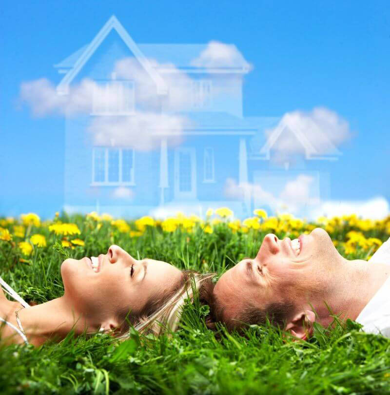 a smiling couple laying in the grass looking up at the sky and thinking about their dream home