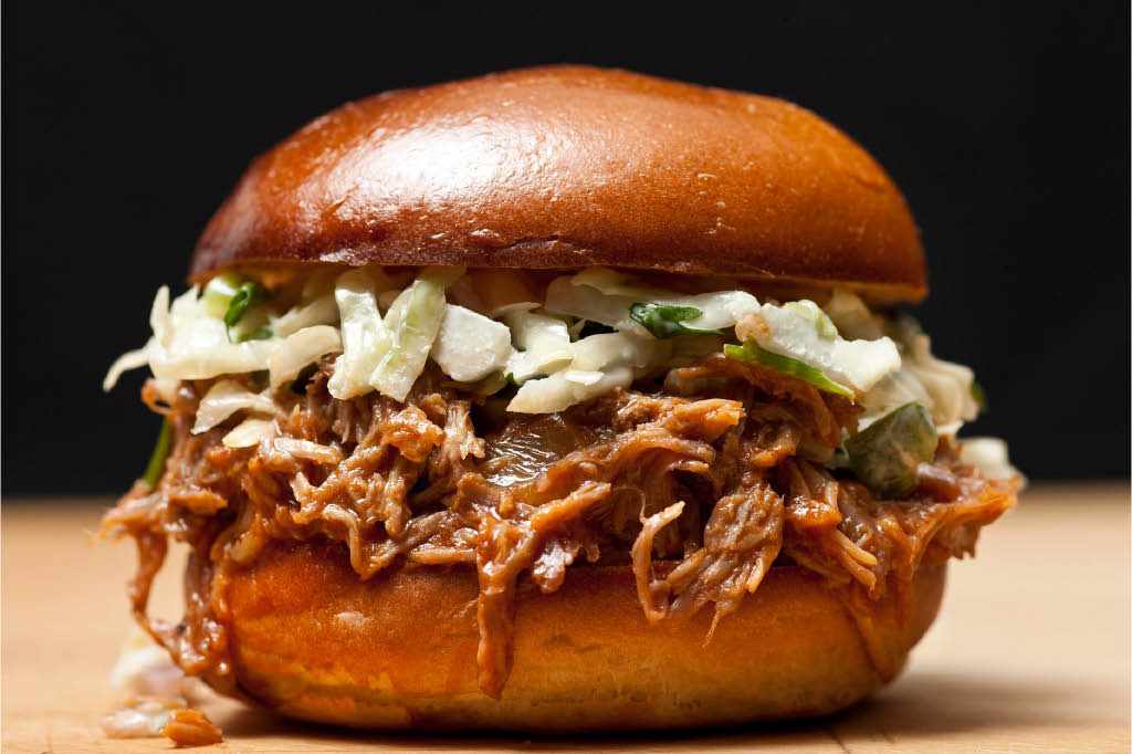 Pulled pork sandwich topped off with green apple slaw.
