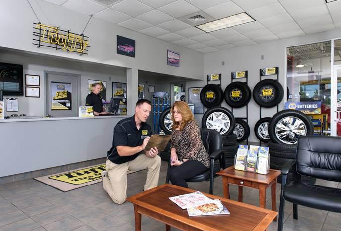 Auto technician explaining service to customer at Tuffy.