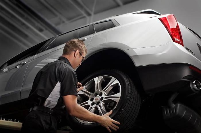 Tuffy auto technician changing tire.