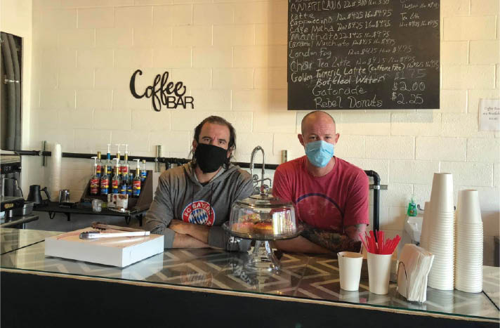 Two baristas serving specialty drinks