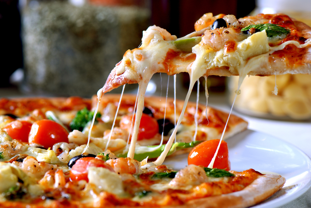Pizza made with tomatoes, black olives and melted mozzarella cheese