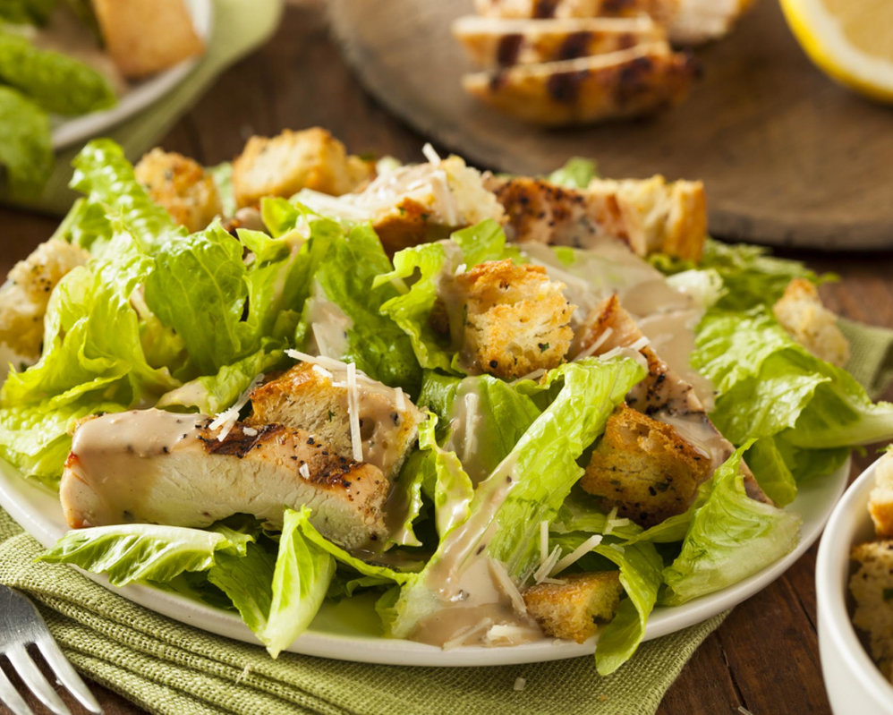 Grilled chicken Caesar salad with lettuce, parmesan cheese, croutons