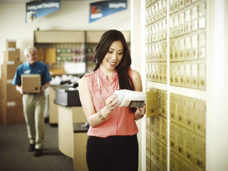 woman checking mail at mailboxes at UPS Store in Carlsbad, CA