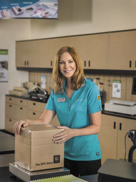 woman in teal shirt weighing a box to be shipped at The UPS Store in Vista, CA