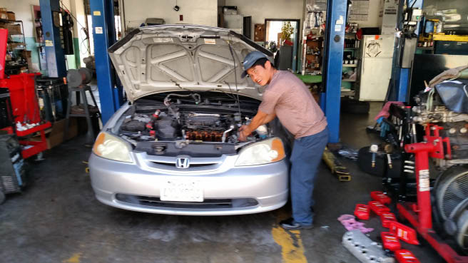 auto mechanic working on car engine at V-TEC in San Marcos, CA