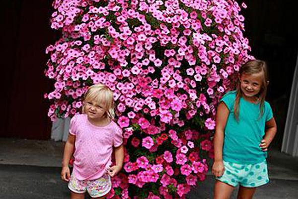 2 of wayne's grand daughters posing in front of a huge hanging flower basket