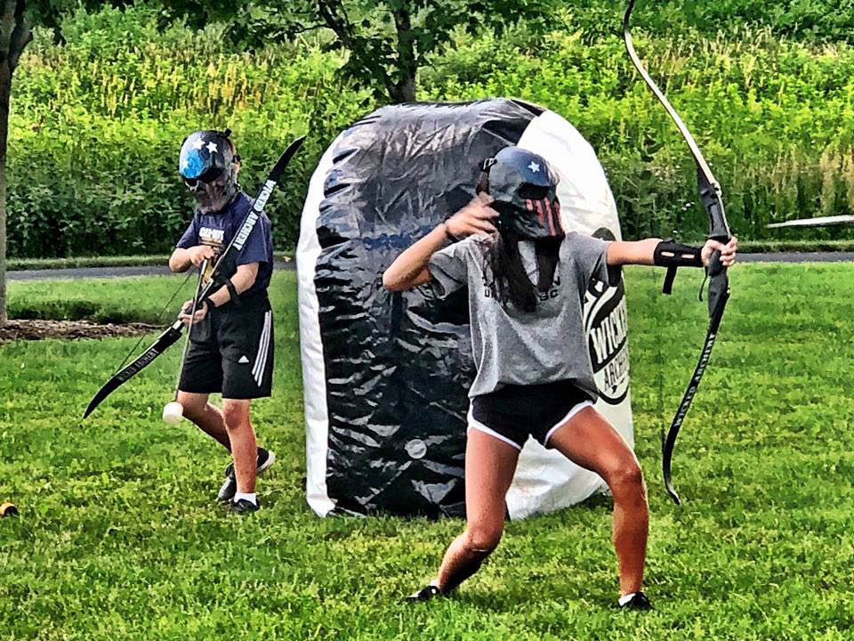 Girl and boy playing Wicked Archery.