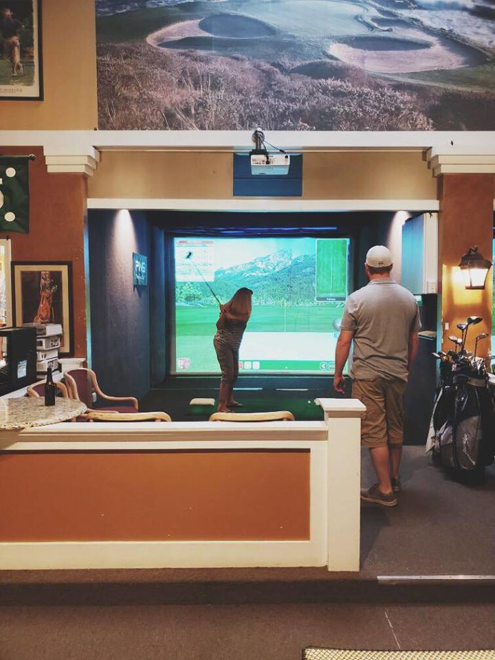 Woman practicing her swing at Indoor Golf Links.