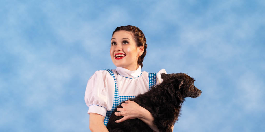 female actor holding a live dog acting as Dorothy from The Wizard of Oz
